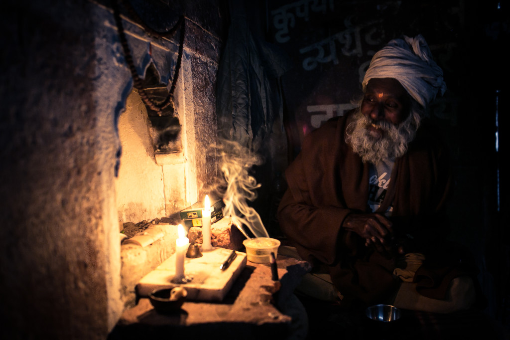 A Sadhu does his morning  rituals and prayers in a dark hallway